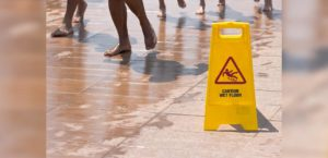 Bare foot people walking on wet floor near yellow wet floor sign.